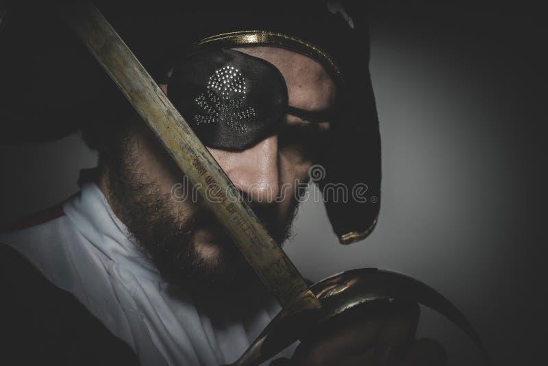 Mannen piratkopierar med ögonlappen och den gamla hatten med roliga framsidor och expre royaltyfri fotografi