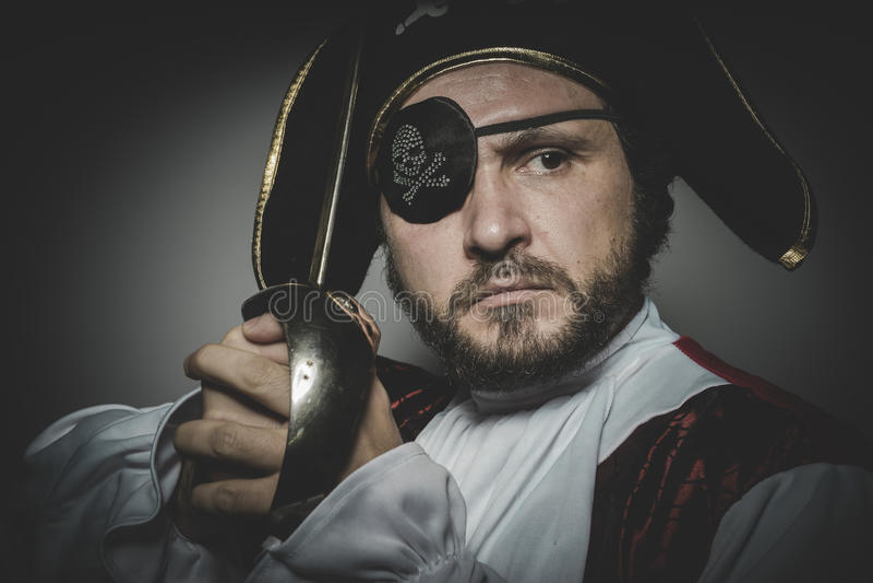 Mannen piratkopierar med ögonlappen och den gamla hatten med roliga framsidor och expre royaltyfri bild