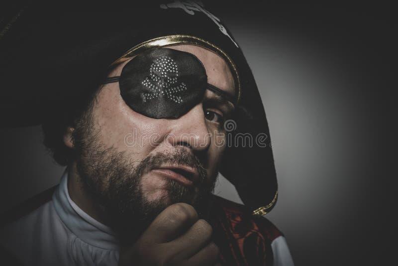 Mannen piratkopierar med ögonlappen och den gamla hatten med roliga framsidor och expre arkivbild
