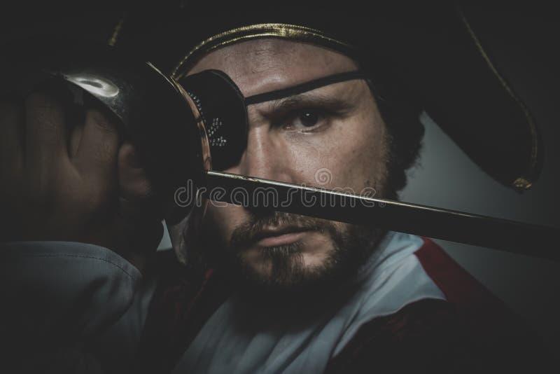 Mannen piratkopierar med ögonlappen och den gamla hatten med roliga framsidor och expre royaltyfri foto