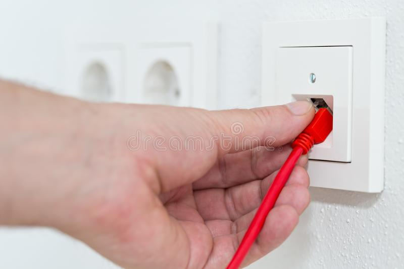 Mannen pluggar på röd nätverkskabel i vägguttag för för LAN-Ethernet för kontoret eller för det privata hemmet anslutning med pla arkivbild