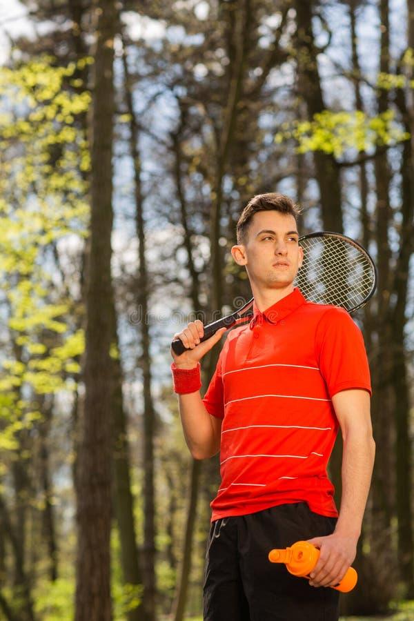 Mannen poserar med en tennisracket, och den orange thermocouplen, p? bakgrunden av gr?splan parkerar begrepp isolerad sportwhite royaltyfria bilder