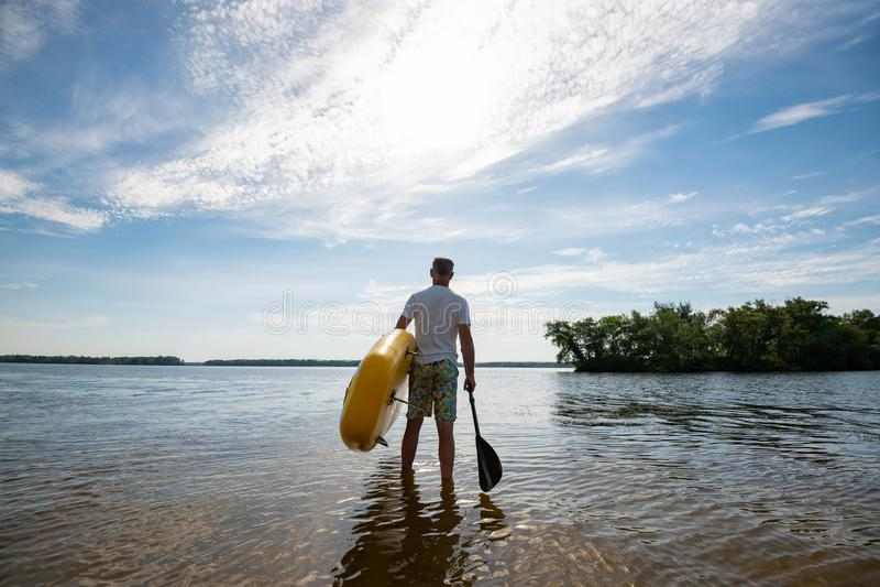 Mannen promenerar stranden med ett SUPbräde och en skovel arkivfoto