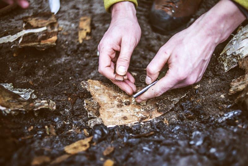 Mannen räcker att försöka att göra brand vid flinta i en skog royaltyfri bild