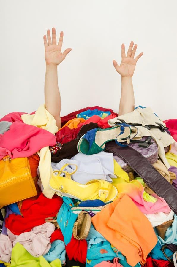 Mannen räcker att nå ut från en stor hög av kläder och tillbehör arkivbild