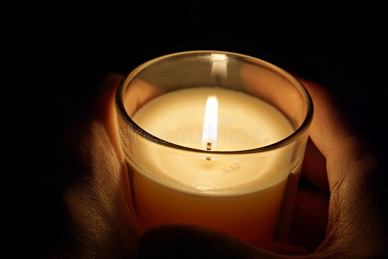 Mannen räcker att rymma en stearinljus i genomskinligt glass skina i mörkret som ett symbol av begrundande, meditationen och lugn royaltyfria bilder