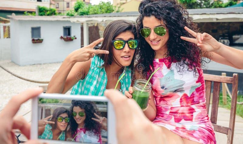 Mannen räcker att ta fotoet till två kvinnor med gröna smoothies arkivfoton