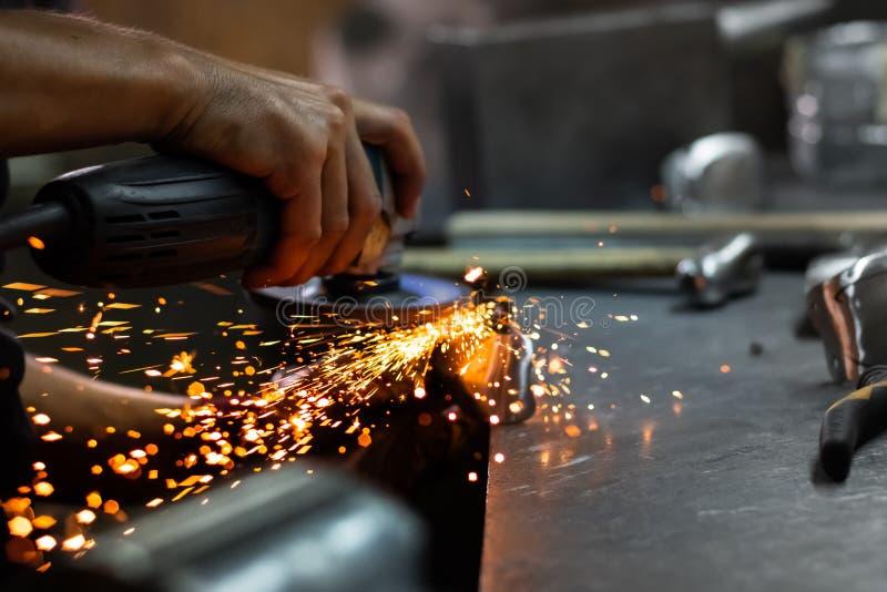 Mannen räcker behandling av metalldelar av maskinvara i ett seminarium med royaltyfri foto