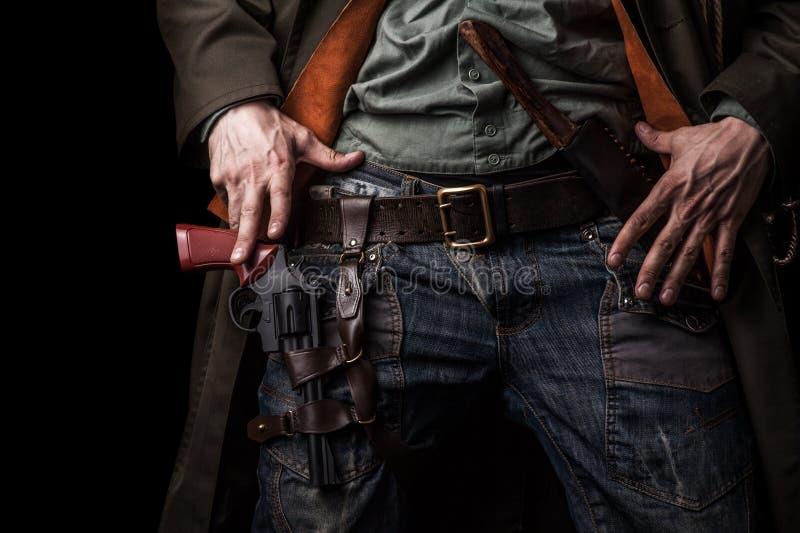 Mannen räcker cowboyen och revolvret på bältet royaltyfri bild