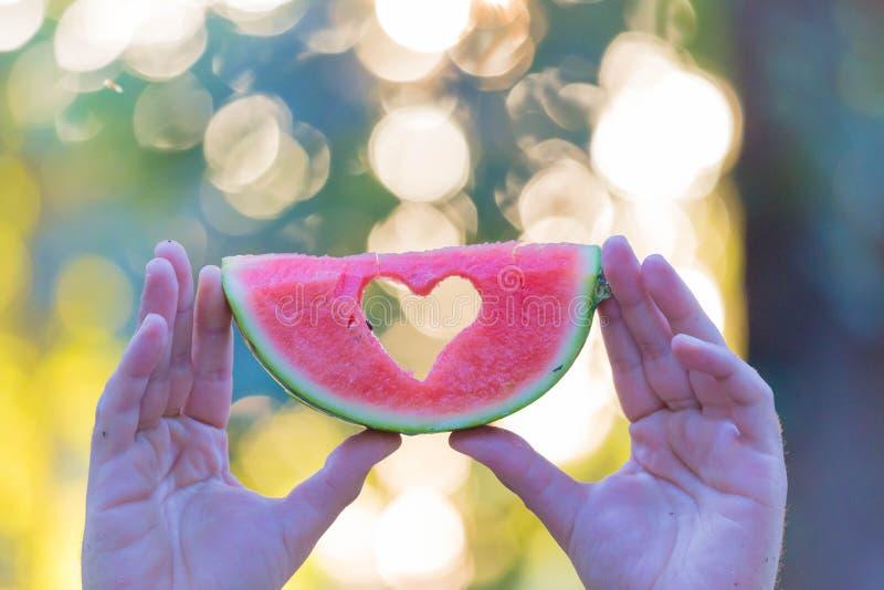 Mannen räcker den hållande vattenmelonskivan med hjärtaform i natur arkivfoto