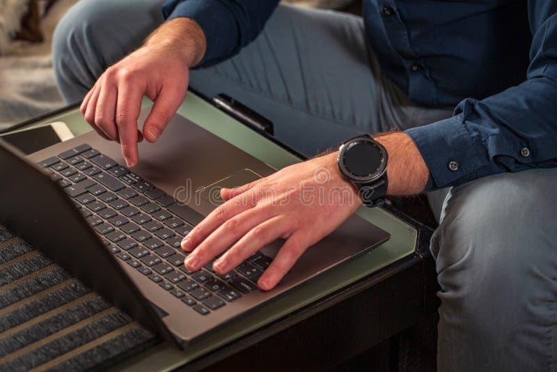 Mannen räcker maskinskrivning på bärbar datortangentbordet royaltyfri fotografi