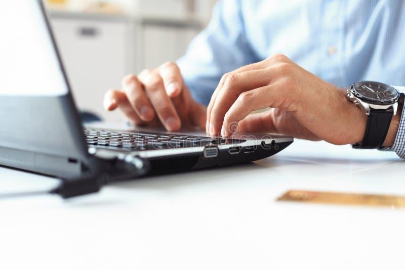 Mannen räcker maskinskrivning på bärbar datortangentbordet arkivbild
