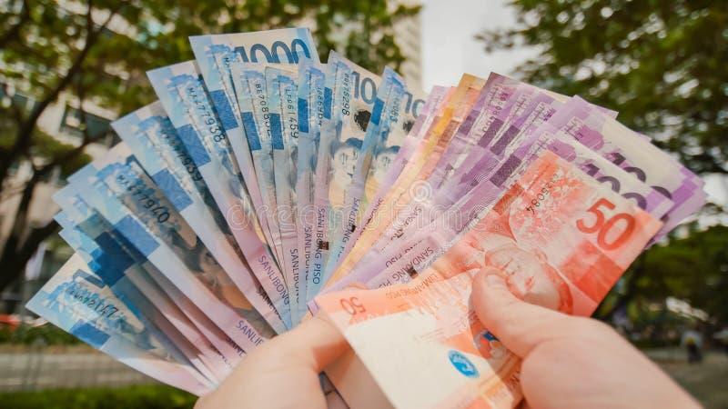 Mannen räknar om de filippinska pengarräkningarna royaltyfria bilder