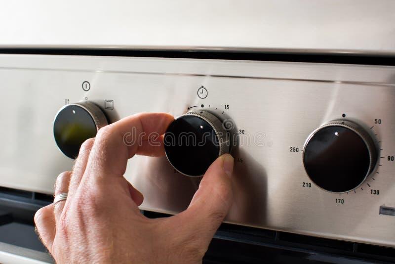 Mannen reglerar temperaturen av ugnen arkivfoto