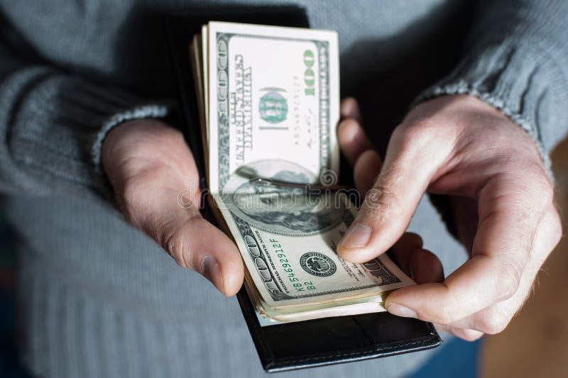 Mannen rensar av kassa ut ur hans plånbok Förmögen man som räknar hans pengar royaltyfri bild