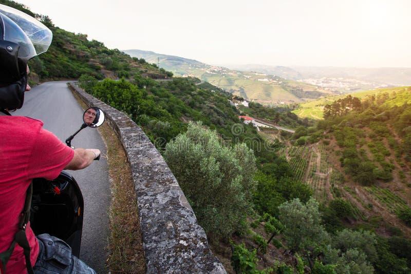 Mannen reser på en motorcykel som stoppas på en siktspunkt på den Douro dalen royaltyfri bild