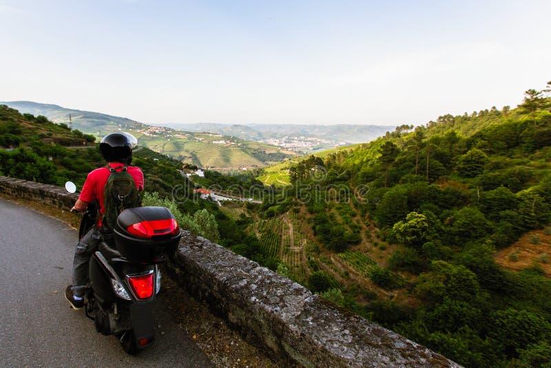 Mannen reser på en motorcykel som stoppas på en siktspunkt och att se den Douro dalen arkivfoto