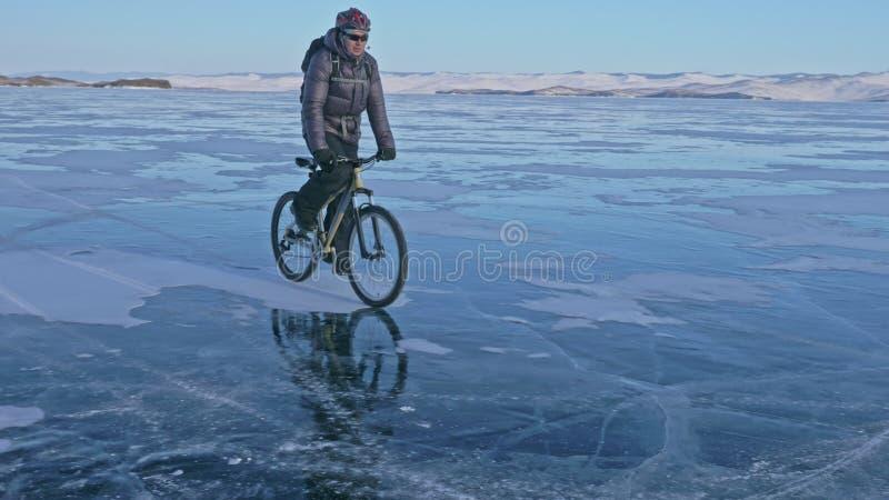 Mannen rider en cykel på is Cyklisten är iklädd en grå färg klår upp ner, ryggsäcken och hjälmen Is av det djupfryst royaltyfria bilder