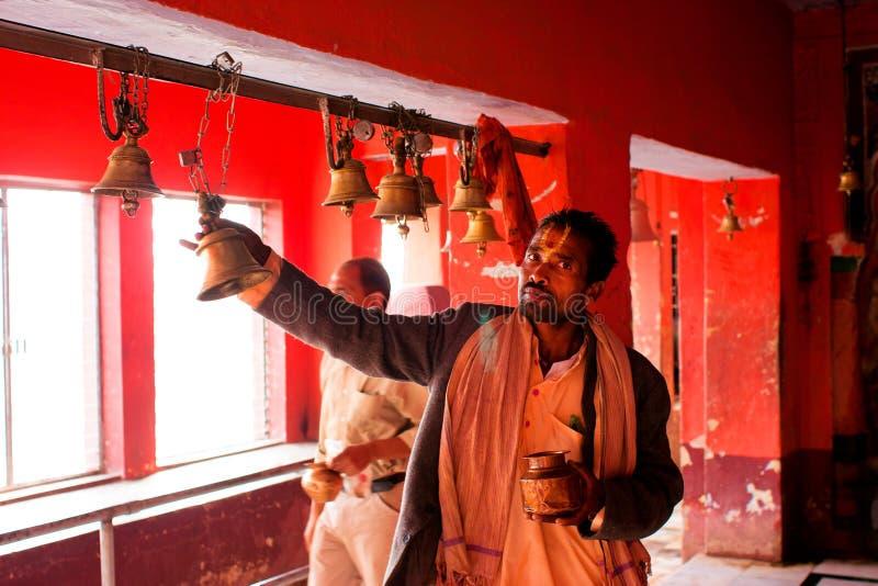 Mannen ringer klockan efter be inom den hinduiska templet arkivbild