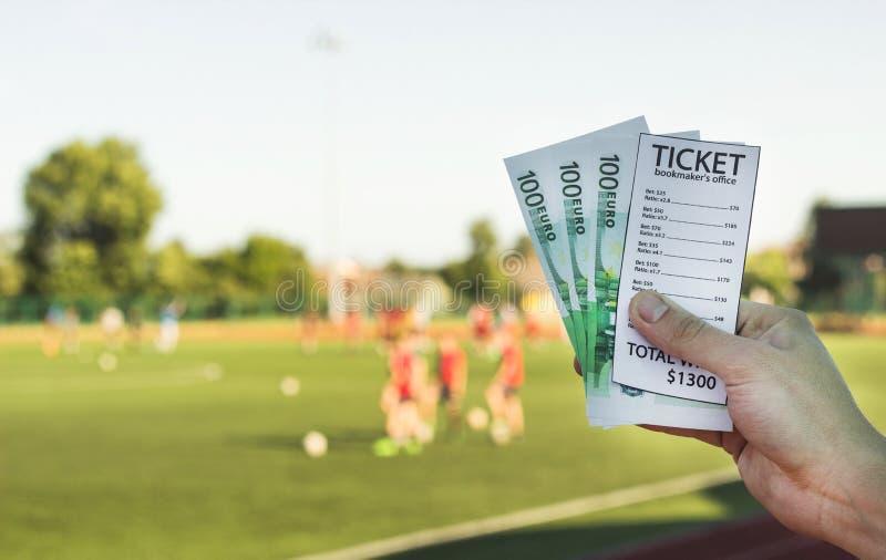 Mannen rymmer en biljett för bookmaker` s och pengareuro i bakgrunden av en stadionfotbolllek, närbild royaltyfri foto