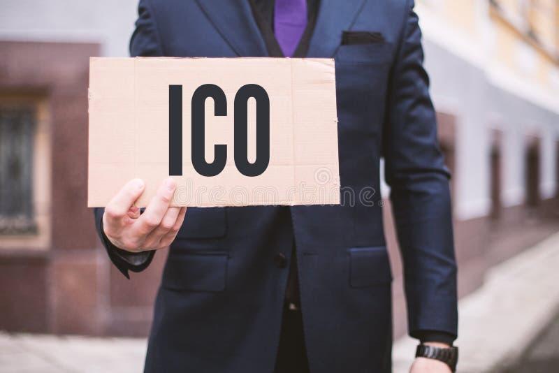 Mannen rymmer ett tecken in hans hand med det initiala myntet Offerering för inskriften 'ICO ' Digital lagerför den elektroniska  royaltyfri fotografi