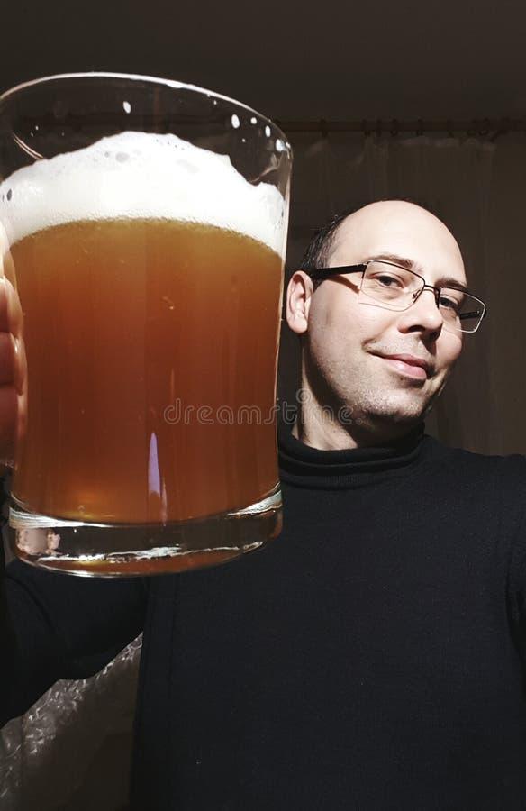 Mannen rymmer exponeringsglas av öl royaltyfri foto