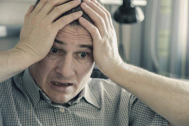 Mannen rymmer hans huvud i hans h?nder Problem i personligt liv och p sp?nning Migr royaltyfri foto