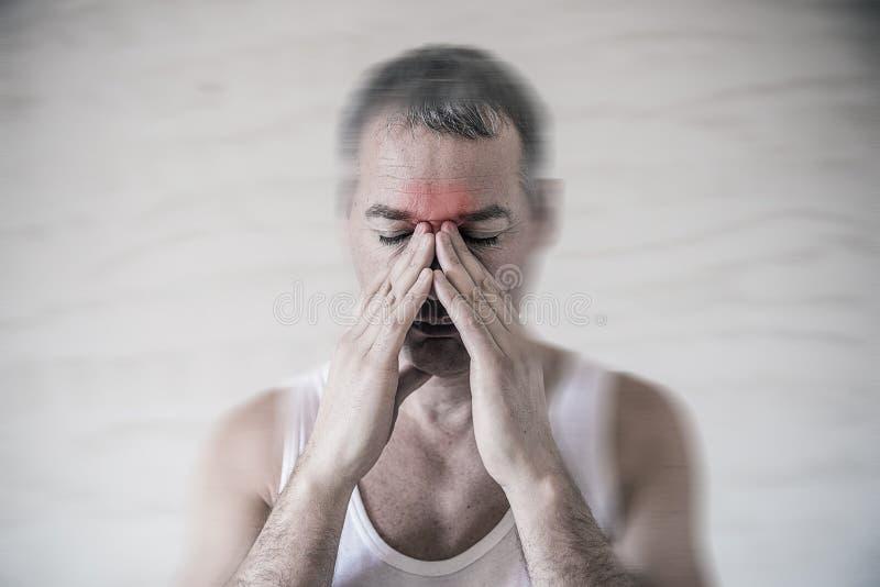 Mannen rymmer hans näsa, och bihålaområde med fingrar i tydligt smärtar från ett pannaområde för head knip framtill royaltyfria bilder