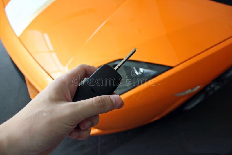 Mannen rymmer tangenten av en lyxig bil royaltyfri bild