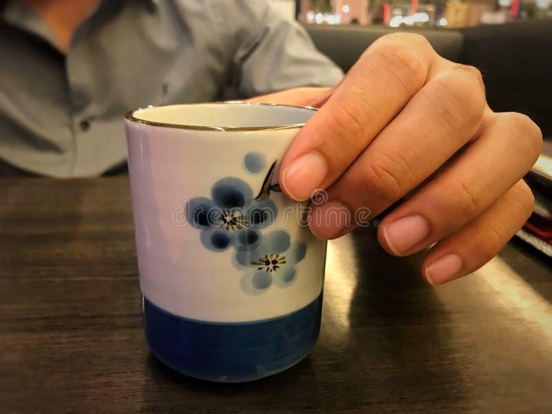 mannen rymmer varmt grönt te keramiskt rånar för att dricka på den japanska restaurangen royaltyfri foto