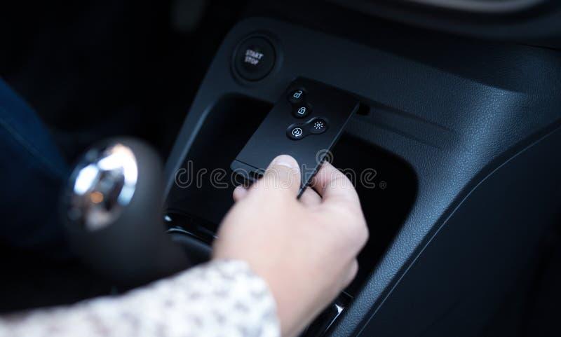 Mannen sätter in det nyckel- kortet in i springan i bilen för att starta motorn royaltyfria bilder