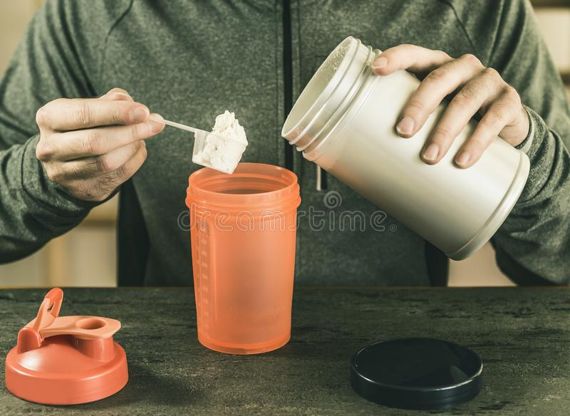 Mannen sätter en del av protein i en shaker, mot en bakgrund av ett mörkt köksbord, en bästa sikt, en sportig livsstil royaltyfria foton