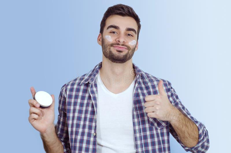 Mannen sätter framsidakräm på kinder som visar upp tummar arkivfoto