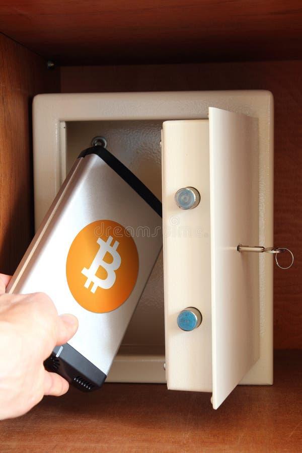 Mannen sätter yttre hårddisk med Bitcoin i kassaskåp royaltyfria bilder