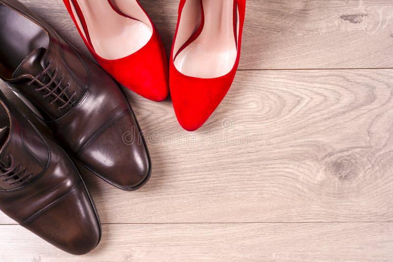 Mannen ` s en de schoenen van rode hoge hielvrouwen op witte achtergrond stock foto's