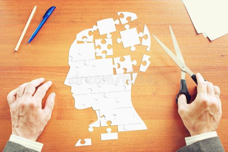 Mannen samlar ett mänskligt huvud som pussel på skrivbordet arkivbild