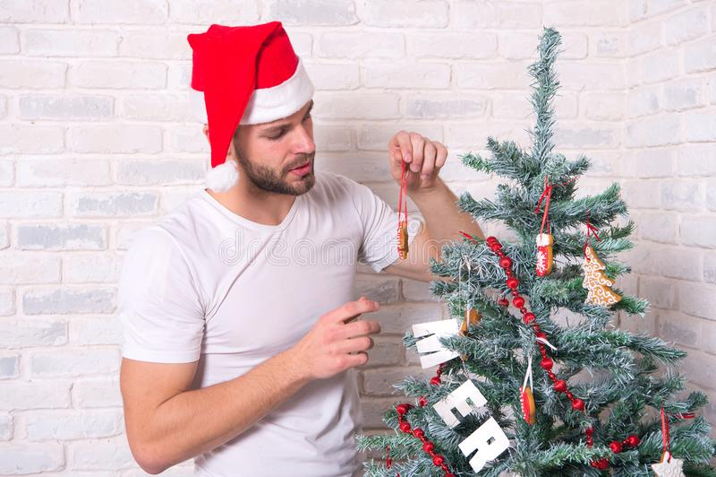 Mannen santa dekorerar julgranen med pepparkakastjärnakakan arkivfoto