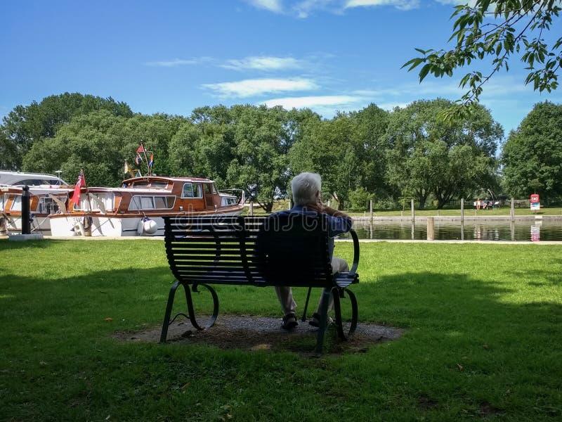 Mannen satt på en plats som beundrar fartygen på den Beccles kajen på floden Waveney royaltyfria foton