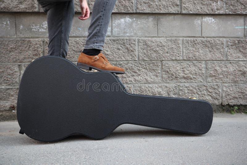 Mannen satte hans fot på ett hårt gitarrfall H?rt fall f?r elektrisk gitarr Iklädd jeans för man som rymmer gitarrfallet mot vägg arkivfoto