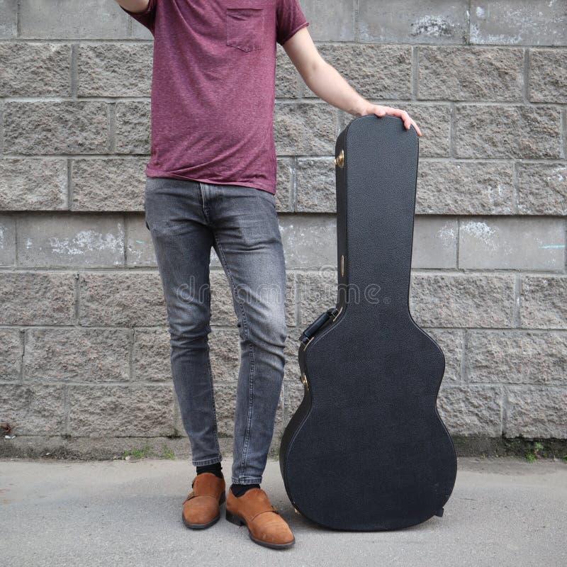Mannen satte hans fot på ett hårt gitarrfall H?rt fall f?r elektrisk gitarr Iklädd jeans för man som rymmer gitarrfallet mot vägg arkivbild