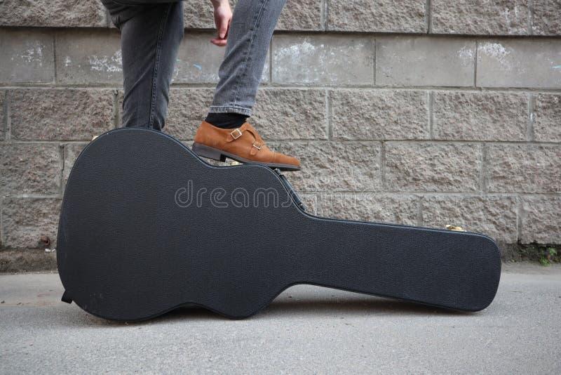 Mannen satte hans fot på ett hårt gitarrfall H?rt fall f?r elektrisk gitarr Iklädd jeans för man som rymmer gitarrfallet mot vägg arkivbilder