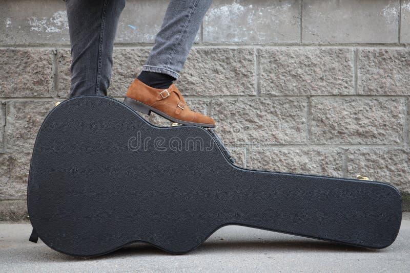 Mannen satte hans fot på ett hårt gitarrfall H?rt fall f?r elektrisk gitarr Iklädd jeans för man som rymmer gitarrfallet mot vägg royaltyfri foto