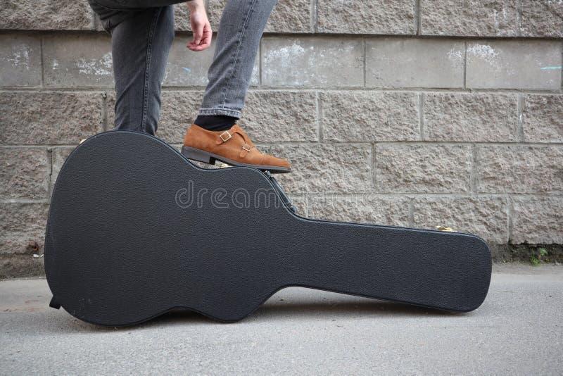 Mannen satte hans fot på ett hårt gitarrfall H?rt fall f?r elektrisk gitarr Iklädd jeans för man som rymmer gitarrfallet mot vägg royaltyfri fotografi