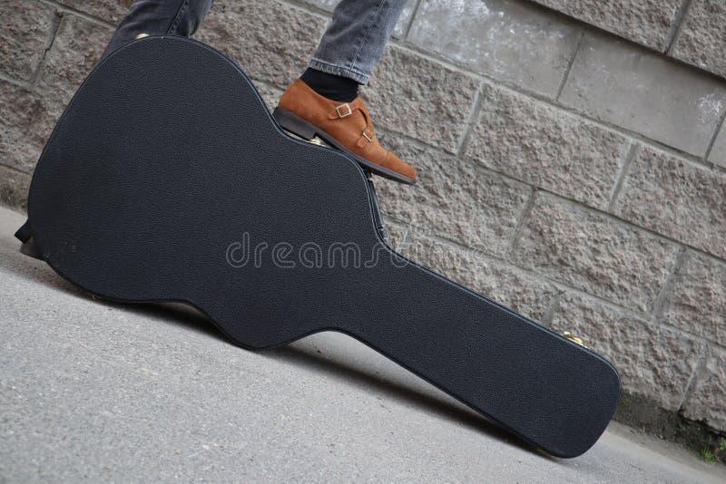 Mannen satte hans fot på ett hårt gitarrfall H?rt fall f?r elektrisk gitarr Iklädd jeans för man som rymmer gitarrfallet mot vägg fotografering för bildbyråer