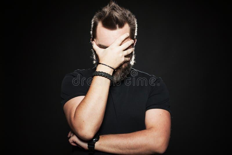 Mannen satte hans hand till hans framsida i studio på en svart bakgrund Honom ledsen ` s som mycket är olycklig och Kroppsspråk F arkivfoton