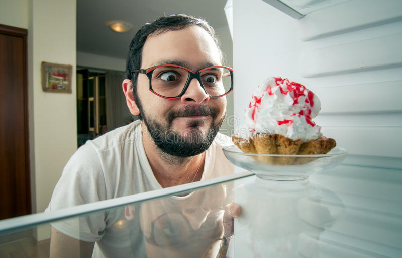 Mannen ser den söta kakan i kylen royaltyfri bild