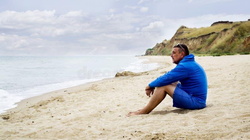 Mannen ser havssammanträdet på en sandig strand rekreation royaltyfri foto