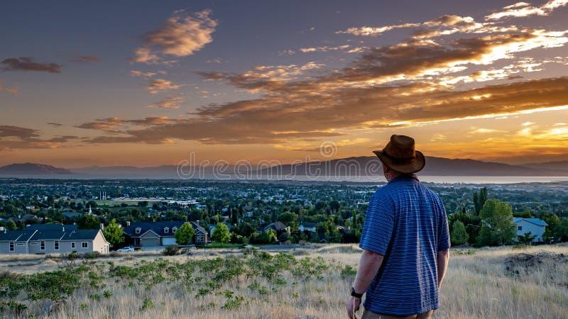 Mannen ser i vördnad på en guld- solnedgång över en fridsam stad royaltyfri foto