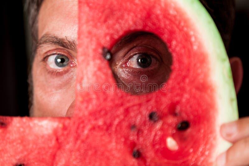 Mannen ser till och med hålet i skiva av den röda vattenmelon arkivfoto