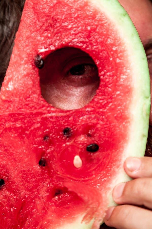 Mannen ser till och med hålet i skiva av den röda vattenmelon arkivbilder